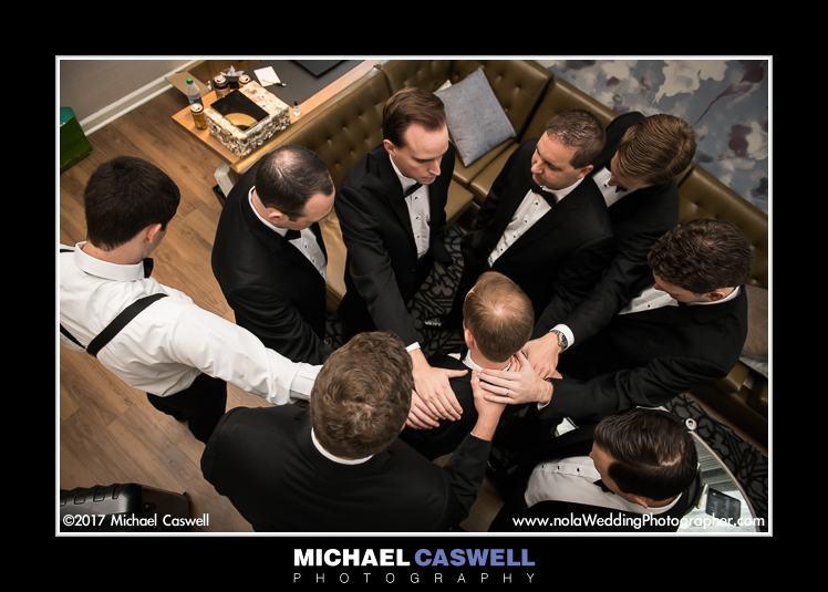 Groom and groomsmen pray before wedding